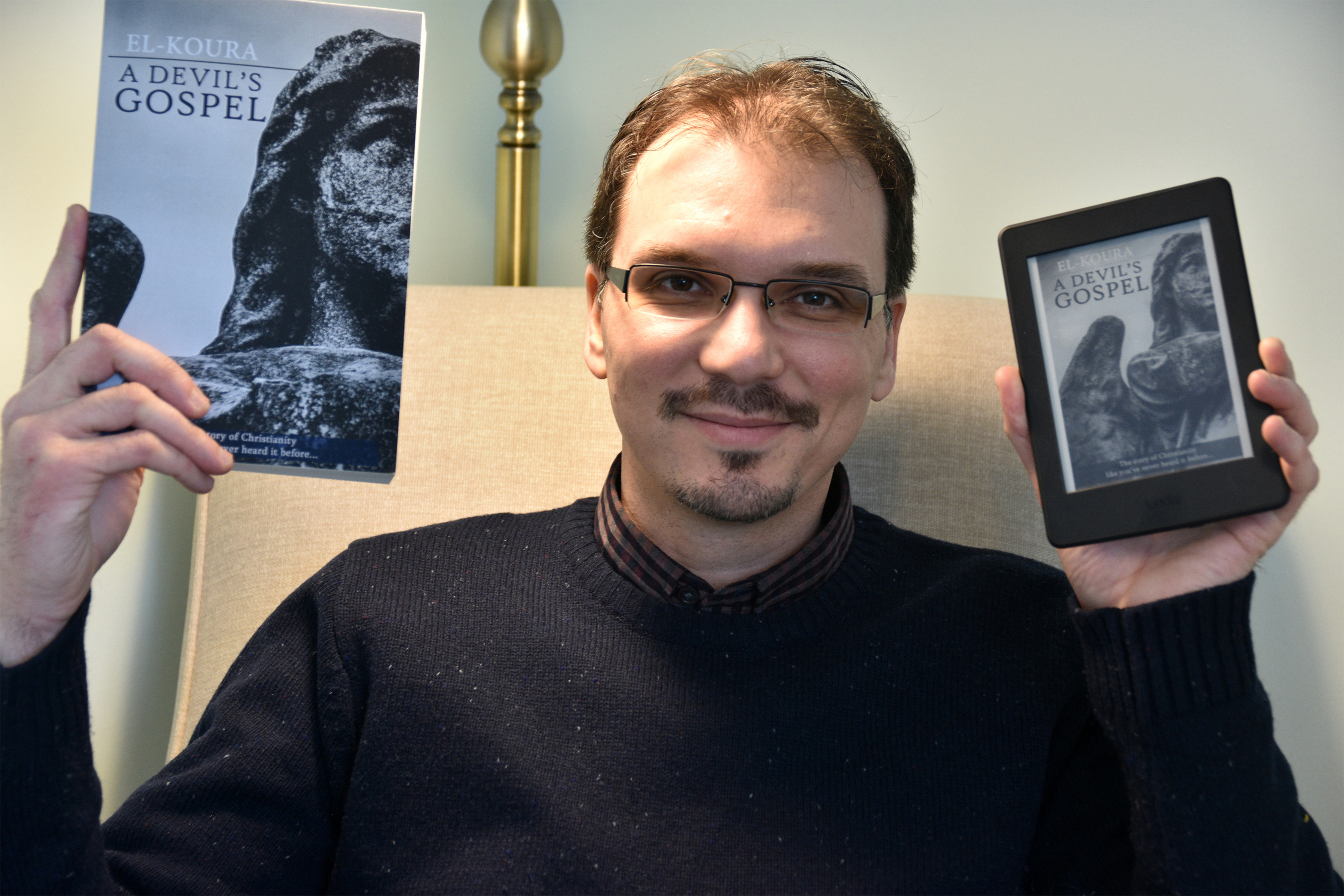 The author holding paperback and ebook copies of A Devil's Gospel